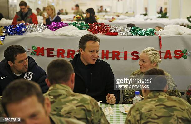 Britain's Prime Minister David Cameron and former England footballer Michael Owen eat breakfast with British soldiers at Camp Bastion outside Lashkar...