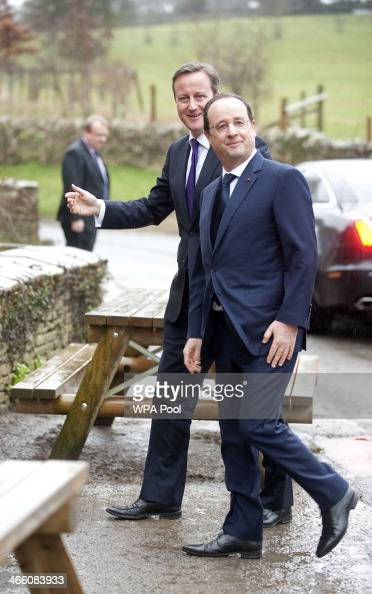 Britain's Prime Minister David Cameron and France's President Francois Hollande arrive for an informal lunch at The Swan Inn pub during their oneday...