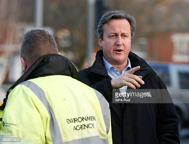 Britain's Prime Minister David Cameron chats to a worker on Warwick Road during a visit to flood hit areas on December 7 2015 in Carlisle England...