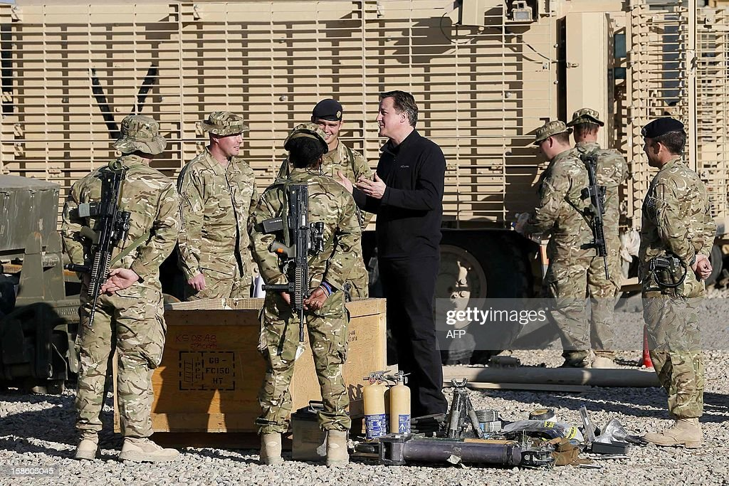 Britain's Prime Minister David Cameron (R) chats with soldiers in front of Mastiff armoured vehicles at Camp Bastion, outside Lashkar Gah in Helmand Province, Afghanistan on December 20, 2012. British Prime Minister David Cameron on December 19, 2012 said that he will withdraw almost half of the country's 9,000 troops from Afghanistan next year as NATO hands over to Afghan forces. AFP PHOTO/POOL/ Stefan Wermuth