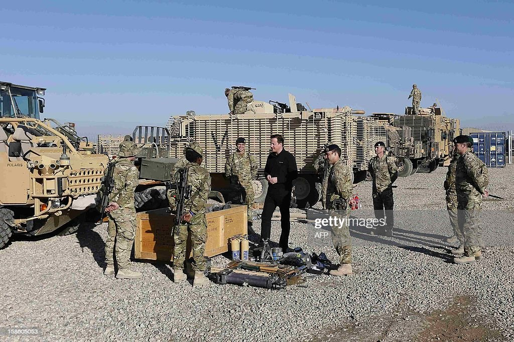 Britain's Prime Minister David Cameron (C) chats with soldiers in front of Mastiff armoured vehicles at Camp Bastion, outside Lashkar Gah in Helmand Province, Afghanistan on December 20, 2012. British Prime Minister David Cameron on December 19, 2012 said that he will withdraw almost half of the country's 9,000 troops from Afghanistan next year as NATO hands over to Afghan forces. AFP PHOTO/POOL/ Stefan Wermuth