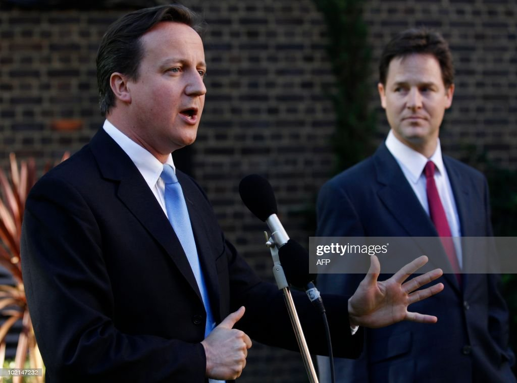Britain's Prime Minister David Cameron (L), flanked by deputy prime minister Nick Clegg (R) addresses guests at the Gay Pride reception in the garden at 10 Downing Street, in central London on June 16, 2010. Same-sex marriage is not legal in the United Kingdom. AFP PHOTO / POOL / Andrew WINNING