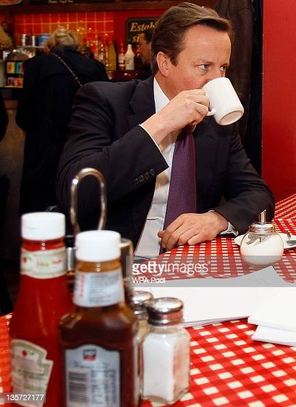 Britain's Prime Minister David Cameron has a drink during a meeting with retail expert Mary Portas on December 13 2011 in Camden London Retail expert...