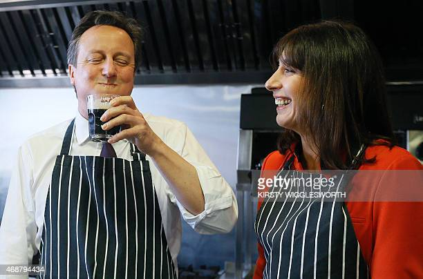 Britain's Prime Minister David Cameron has a sip of stout by his wife Samantha during a visit to Brains Brewery in Cardiff Wales on April 7 2015...