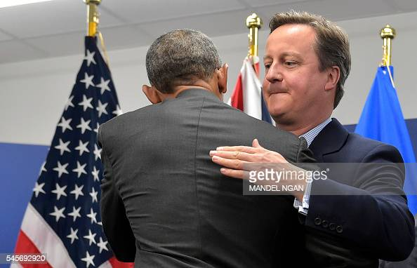 TOPSHOT Britain's Prime Minister David Cameron hugs US President Barack Obama after a quint meeting during the NATO Summit at the Polish National...