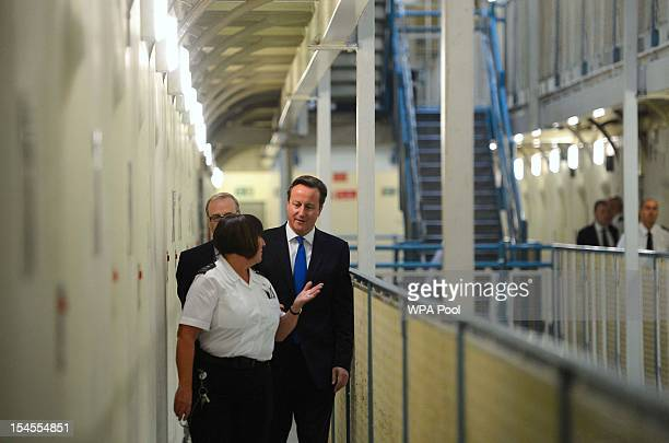 Britain's Prime Minister David Cameron is escorted around C wing by prison officer Margaret Vaughan and Governor Phil Taylor during his visit to...
