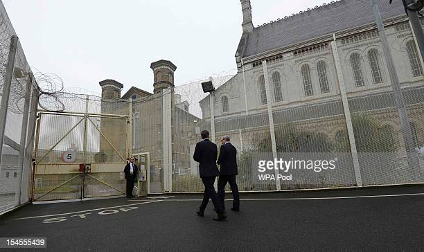 Britain's Prime Minister David Cameron is escorted by prison governor Phil Taylor for a visit to Wormwood Scrubs Prison on October 22 2012 in London...