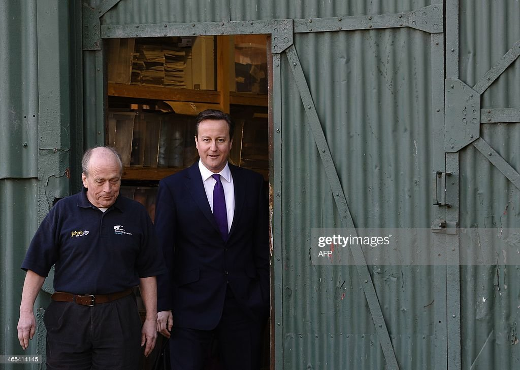 Britain's Prime Minister David Cameron (R) is taken for a tour by boat builder and restorer John Watson (L) during a visit to small businesses at Lots Ait Boatyard in Brentford, west London, on January 27, 2014. Cameron told company owners that his government has exceeded its targets for cutting back over-zealous business regulations and will save firms millions of pounds per year.