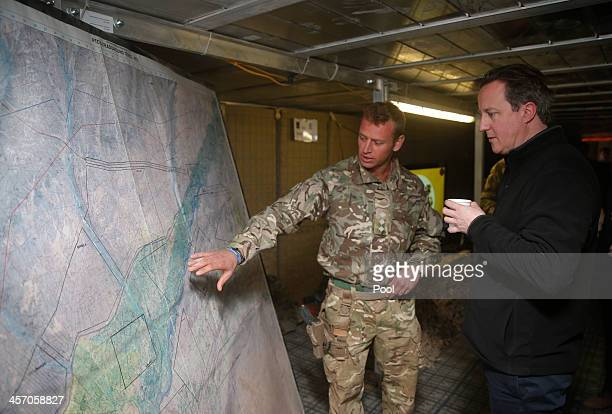 Britain's Prime Minister David Cameron listens to a briefing by a British army officer at the forward operating base Sterga II on December 16 2013 in...