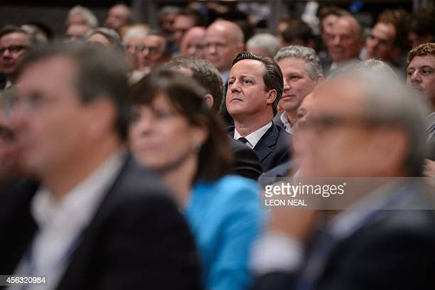Britain's Prime Minister David Cameron listens to a speech by Chancellor of the Exchequer George Osborne during the second say of the Conservative...