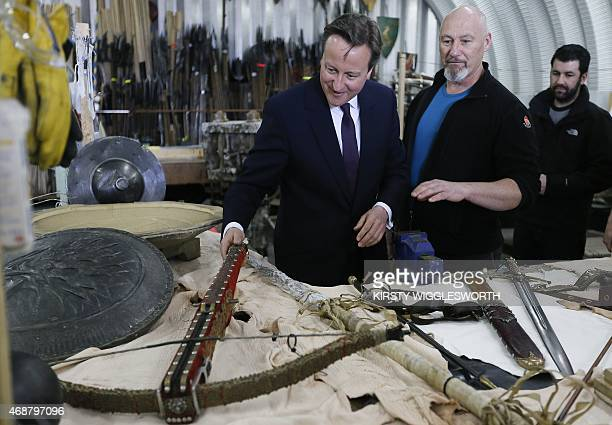 Britain's Prime Minister David Cameron looks at a crossbow in a workshop during a visit to the television set of popular TV fantasy drama Game of...