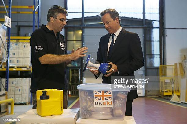 Britain's Prime Minister David Cameron looks at a Sunlite solar lantern that also recharges mobile phones as he talks to Julian Neale Procurement and...