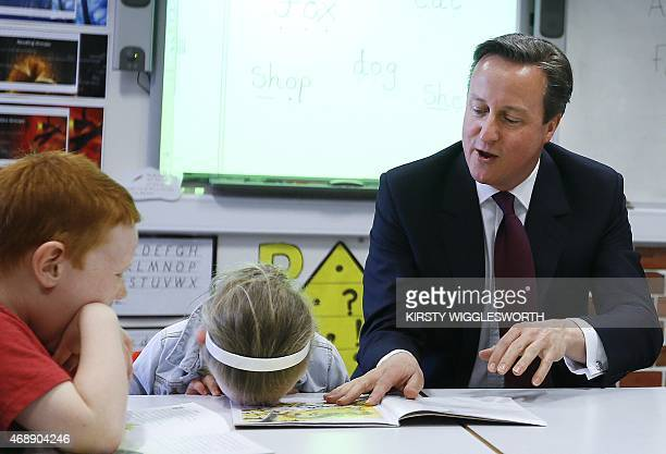Britain's Prime Minister David Cameron reads a book to Lucy Howarth and Will Spibey during a visit to Sacred Heart RC primary school in Westhoughton...