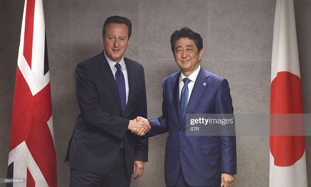 Britain's Prime Minister David Cameron (L) shakes hands with Japanese Prime Minister Shinzo Abe in Ise city, Mie prefecture on May 25, 2016, ahead of the G7 summit. / AFP / JAPAN POOL / STR / Japan OUT / JAPAN