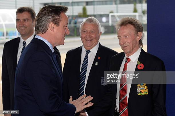 Britain's Prime Minister David Cameron shares a joke with former Manchester United player Denis Law during a visit to the City Football Academy on...