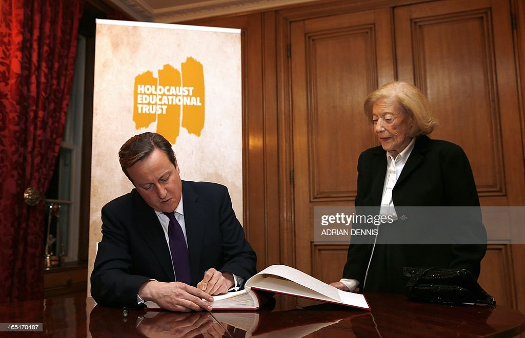 Britain's Prime Minister David Cameron signs a book of commitment for the Holocaust Educational Trust during a reception at 10 Downing Street in central London January 27, 2014, for survivors of the Holocaust and other genocides to commemorate Holocaust Memorial Day. Actress Helena Bonham Carter, broadcaster Natasha Kaplinsky and chief rabbi Ephraim Mirvis will sit on a commission examining ways to remember and learn about the Holocaust, Downing Street has announced.