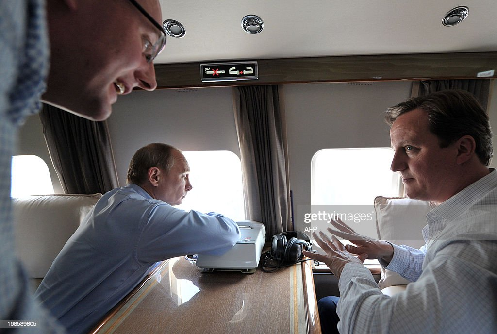 Britain's Prime Minister David Cameron (R) speaks as he and Russian President Vladimir Putin (C) fly by helicopter to inspect the 2014 Winter Olympic facilities after their meeting at the Bocharov Ruchei state residence in Sochi on May 10, 2013. Britain and Russia on May 10 sought to forge a joint approach to the crisis in Syria, as US Secretary of State John Kerry said there was 'strong evidence' Damascus had used chemical weapons against rebels. AFP PHOTO / RIA NOVOSTI / PRESDIENTIAL PRESS SERVICE / ALEXEY NIKOLSKY
