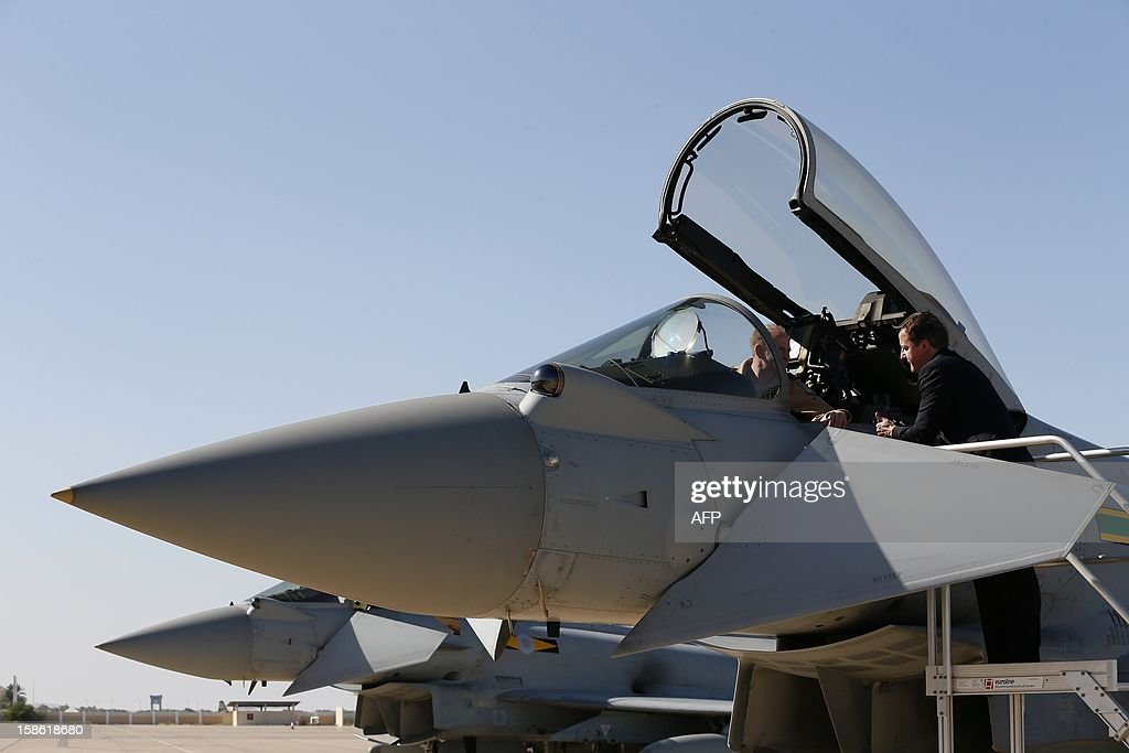 Britain's Prime Minister David Cameron speaks to a pilot in the cockpit of a Typhoon fighter jet during a visit to Muscat, Oman on December 21, 2012. British defence giant BAE Systems unveiled on December 21, 2012 a £2.5-billion ($4.1-billion, 3.1-billion-euro) deal to sell 12 Eurofighter Typhoon combat jets and eight Hawk trainer planes to Oman. The deal, which will help sustain thousands of jobs in Britain, is the first major order since BAE Systems failed to merge with European aerospace giant EADS earlier this year, but failed to boost shares in the British company. AFP PHOTO/POOL/Stefan Wermuth