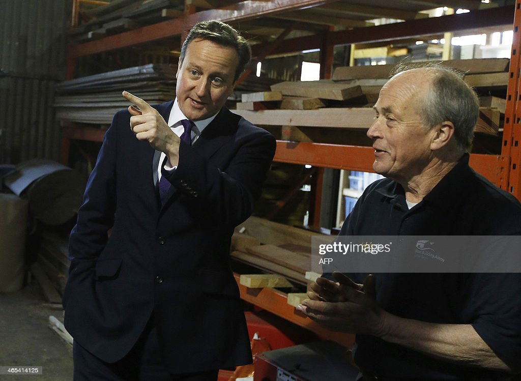 Britain's Prime Minister David Cameron (L) speaks with boat builder and restorer John Watson (R) during a visit to small businesses at Lots Ait Boatyard in Brentford, west London, on January 27, 2014. Cameron told company owners that his government has exceeded its targets for cutting back over-zealous business regulations and will save firms millions of pounds per year.