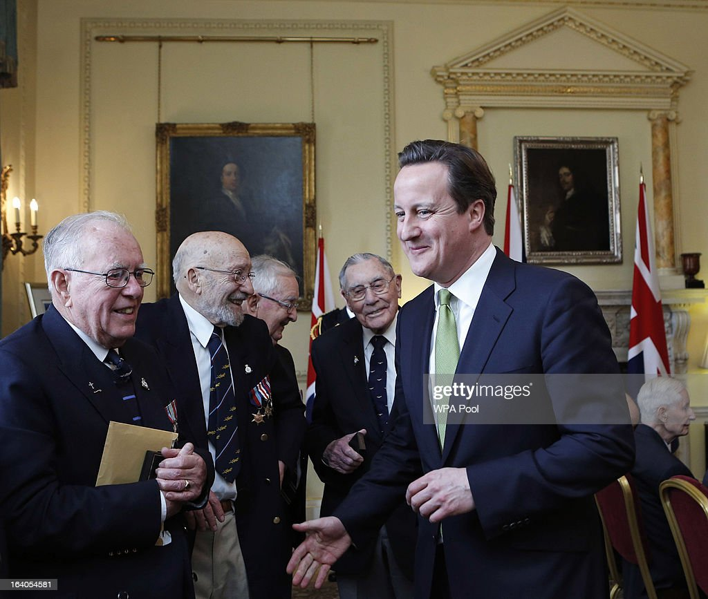 Britain's Prime Minister <a gi-track='captionPersonalityLinkClicked' href=/galleries/search?phrase=David+Cameron+-+Politician&family=editorial&specificpeople=227076 ng-click='$event.stopPropagation()'>David Cameron</a> speaks with World War II veterans after presenting them with a Bomber Command clasp at Number 10 Downing Street on March 19, 2013 in London, England. The PM today presented two newly created medals, 68 years after the Second World War ended.