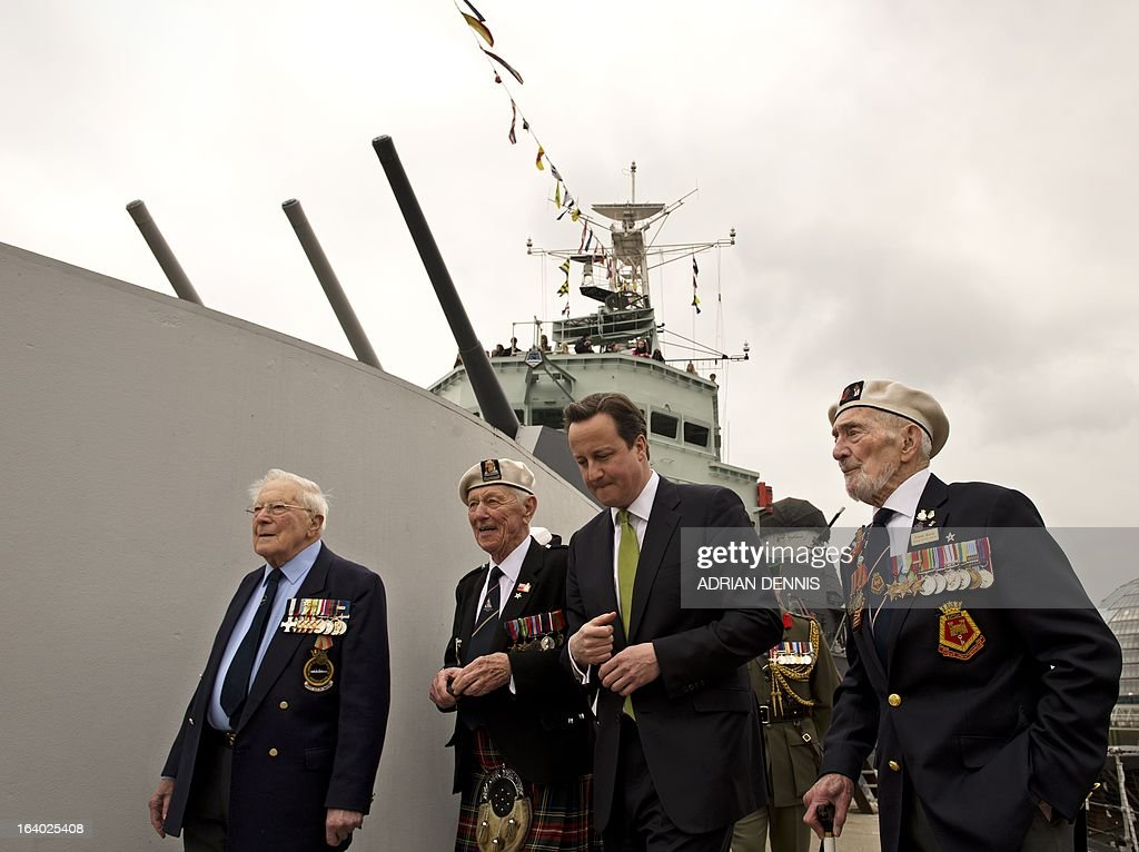 Britain's Prime Minister David Cameron (2R) walks along the deck of decommissioned warship HMS Belfast with WWII veterans Lt Cdr Dick Dykes (L), Jock Dempster (2L) and HMS Belfast veteran Frank Bond (R) on the river Thames in London on March 19, 2013. Cameron hailed the first recipients of the Arctic Star medal as a 'group of heroes', as he presented them with the newly-created award during a ceremony at Downing Street on March 19. The creation of the Arctic Star medal, along with the new Bomber Command Clasp, were announced in December 2012, 67 years after the war, following a long-running campaign. The new Arctic Star rewards World War II war heroes who served on the Arctic Convoys on ships including HMS Belfast on missions to keep open supply lines to Soviet ports from 1941, travelling what Winston Churchill dubbed the 'worst journey in the world'.
