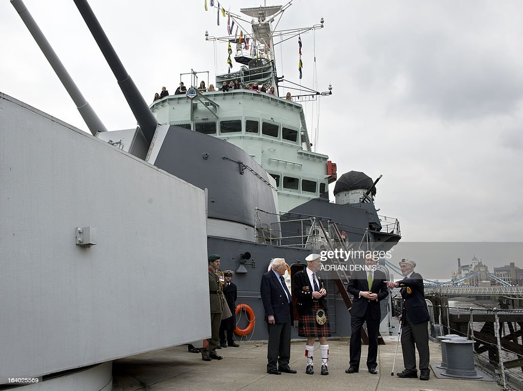 Britain's Prime Minister David Cameron (2R) walks along the deck of decommissioned warship HMS Belfast with WWII veterans Lt Cdr Dick Dykes (L), Jock Dempster (2nd L) and HMS Belfast veteran Frank Bond (R) at its mooring on the river Thames in London on March 19, 2013. Cameron hailed the first recipients of the Arctic Star medal as a 'group of heroes', as he presented them with the newly-created award during a ceremony at Downing Street on March 19. The creation of the Arctic Star medal, along with the new Bomber Command Clasp, were announced in December 2012, 67 years after the war, following a long-running campaign. The new Arctic Star rewards World War II war heroes who served on the Arctic Convoys on ships including HMS Belfast on missions to keep open supply lines to Soviet ports from 1941, travelling what Winston Churchill dubbed the 'worst journey in the world'. AFP PHOTO / POOL / ADRIAN DENNIS