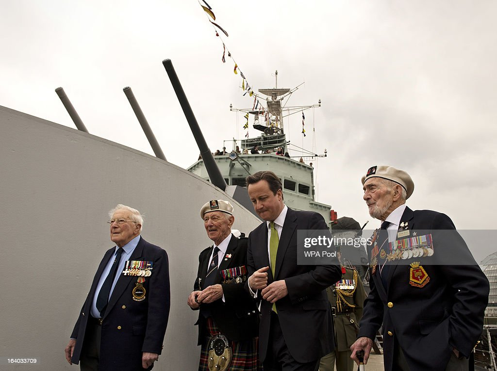 Britain's Prime Minister David Cameron (2nd R) walks along the deck of warship HMS Belfast with WWII veterans Lt. Cdr Dick Dykes (L) Jock Dempster (2nd L), and HMS Belfast veteran Frank Bond (R) on March 19, 2013 in London, England. The PM today presented two newly created medals, 68 years after the Second World War ended.