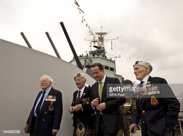 Britain's Prime Minister David Cameron walks along the deck of warship HMS Belfast with WWII veterans Lt Cdr Dick Dykes Jock Dempster and HMS Belfast...