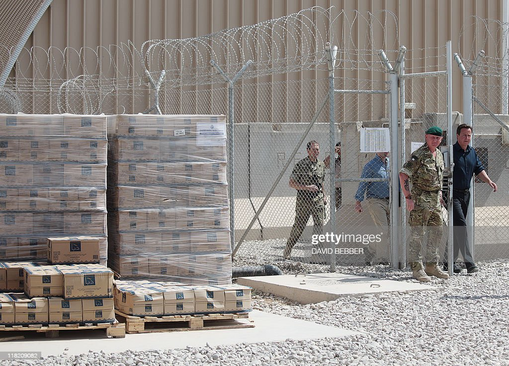 Britain's Prime Minister David Cameron walks past cases of bottled water after a briefing at Camp Bastion military base outside Lashkar Gah the...