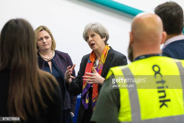 Britain's Prime Minister Theresa May accompanied by local prospective Conservative candidate Mary Macleod speaks to workers during her tour of the...