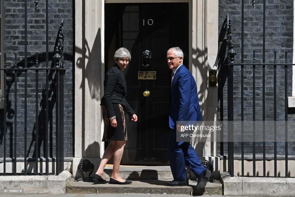Britain's Prime Minister Theresa May (L) and Australian Prime Minister, Malcolm Turnbull turn to enter 10 Downing Street in central London on July 10, 2017. / AFP PHOTO / Ben STANSALL