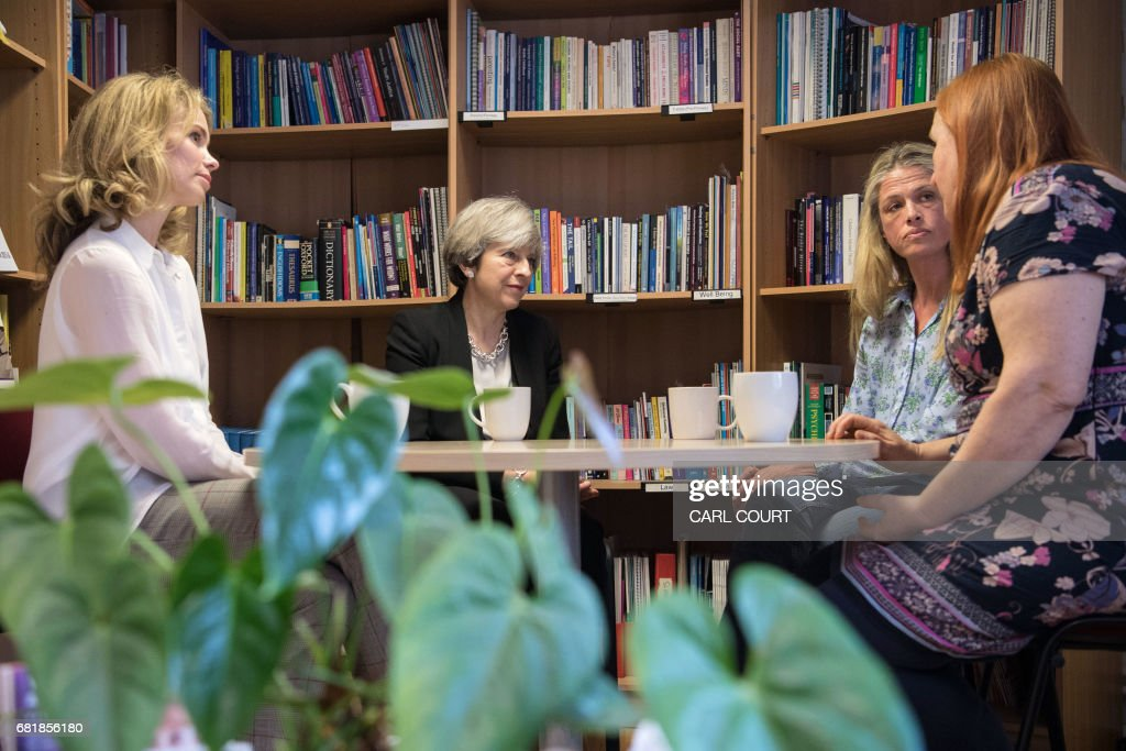 Britain's Prime Minister Theresa May (2L) and Conservative parliamentary candidate for Bermondsey and Old Southwark, Siobhan Baillie (L) meet staff members during a visit to the Young Minds mental health charity in London on May 11, 2017, ahead of the upcoming general election. / AFP PHOTO / POOL / Carl Court