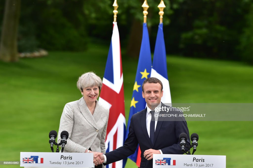 Britain's Prime Minister Theresa May (L) and France's President Emmanuel Macron shake hands during a joint press conference in the grounds of The Elysee Palace in Paris on June 13, 2017. /