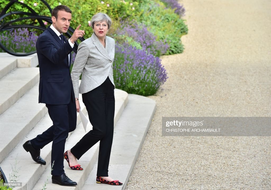 Britain's Prime Minister Theresa May (R) and France's President Emmanuel Macron walk together following a meeting to give a joint press conference in the grounds of The Elysee Palace in Paris on June 13, 2017. /