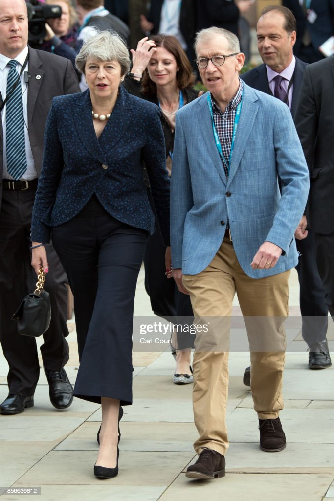 Britain's Prime Minister, Theresa May, and her husband Philip, walk to attend a speech on day two of the Conservative Party Conference at Manchester Central on October 2, 2017 in Manchester, England. Chancellor Philip Hammond announced an extra GBP 300m to improve rail land transport links in northern England as part of the Northern Powerhouse initiative.