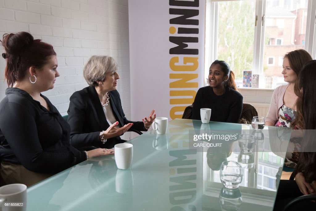 Britain's Prime Minister Theresa May (2L) chats with youth activists during a visit to the Young Minds mental health charity in London on May 11, 2017, ahead of the upcoming general election. / AFP PHOTO / POOL / Carl Court