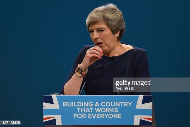 Britain's Prime Minister Theresa May coughs as she delivers her speech on the final day of the Conservative Party annual conference at the Manchester...