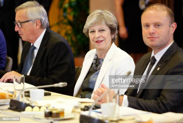 Britain's Prime Minister Theresa May flanked by European Commission President JeanClaude Juncker speaks with Malta's Prime Minister Joseph Muscat...