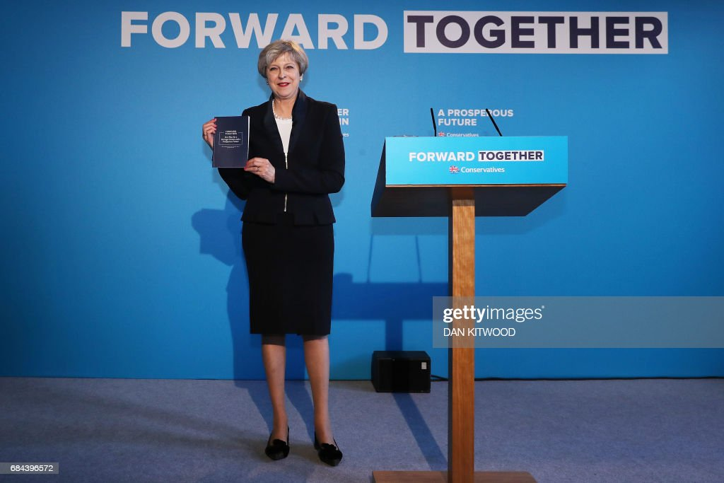 Britain's Prime Minister Theresa May holds up the Conservative Party general election manifesto as she speaks at the launch event in Halifax in northern England on May 18, 2017. British Prime Minister Theresa May will on May 18 promise to crack down on immigration from outside the European Union as she unveils the Conservative Party's manifesto. / AFP PHOTO / POOL / Dan Kitwood