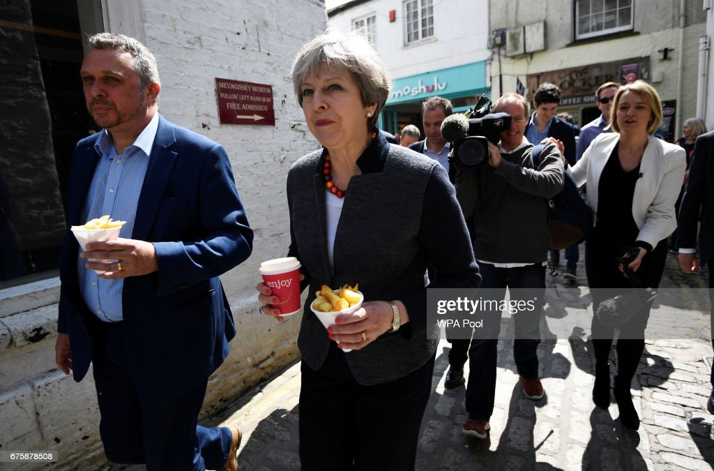 Britain's Prime Minister Theresa May is followed by journalists as she carries some chips during a campaign stop on May 2, 2017 in Mevagissey, Cornwall, England. The Prime Minister is campaigning in South-West England, a former Liberal Democrat stronghold, as she urges West Country voters to stick with her party ahead of the polls on June 8.