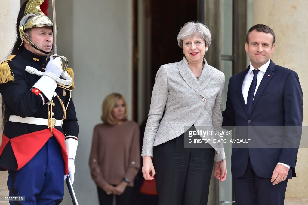 Britain's Prime Minister Theresa May is greeted by France's President Emmanuel Macron ahead of a meeting at The Elysee Palace in Paris on June 13, 2017. /