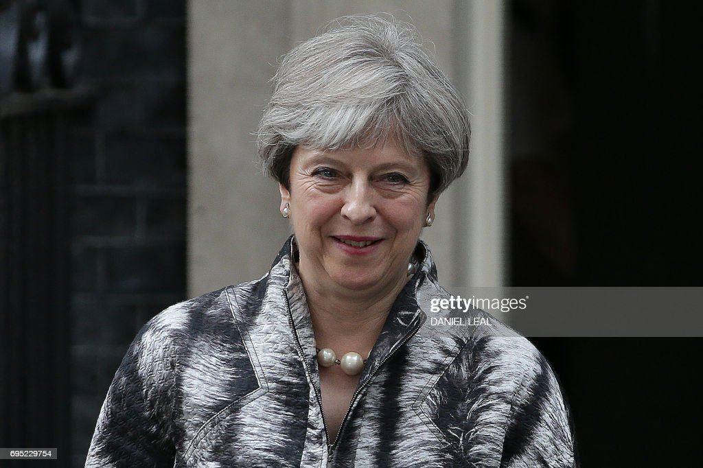 Britain's Prime Minister Theresa May (L) leaves after hosting a Cabinet meeting at 10 Downing Street in central London on June 12, 2017, following the June 8 snap general election in which the ruling Conservatives lost their majority. Britain's embattled Prime Minister Theresa May on Sunday unveiled her full cabinet, making few changes as the premier clings to power after losing her parliamentary majority in a snap election. / AFP PHOTO / Daniel LEAL