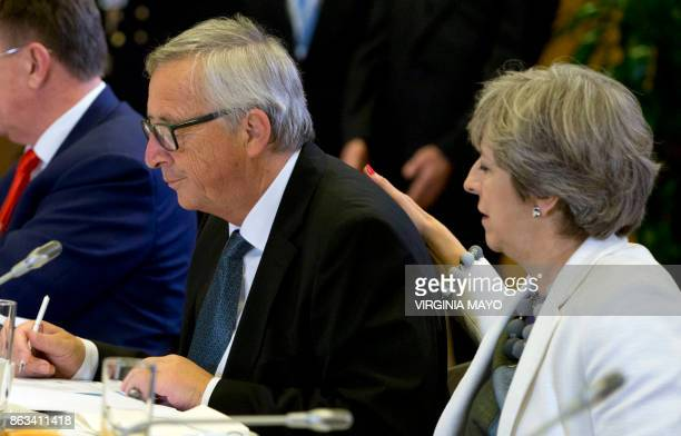 Britain's Prime Minister Theresa May places her hand on the back of European Commission President JeanClaude Juncker during a breakfast meeting at on...