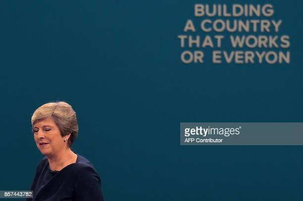 Britain's Prime Minister Theresa May reacts as she acknowledges applause from delegates while passing a slogan whose letters have fallen off after...