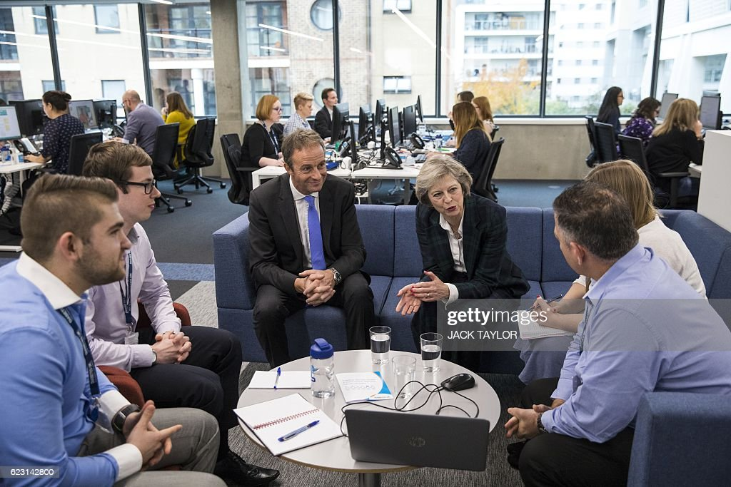 Britain's Prime Minister Theresa May (3R) seated next to charity Diabetes UK Chief Executive Chris Askew (3L) speaks with helpline staff at the charity's new office in London on November 14, 2016. May, who has been diagnosed with Type 1 diabetes, officially opened the new Diabetes UK office today to coincide with World Diabetes Day. / AFP / POOL / Jack Taylor