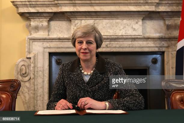 Britain's Prime Minister Theresa May signs the official letter to European Council President Donald Tusk invoking Article 50 and signalling the...
