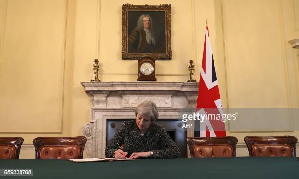 Britain's Prime Minister Theresa May sits below a painting of Britain's first Prime Minister Robert Walpole as she signs the official letter to...