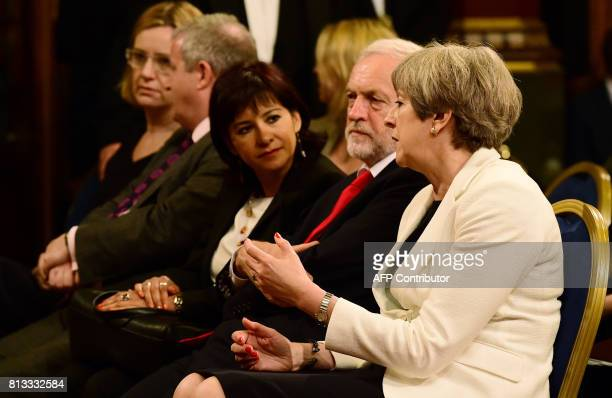 Britain's Prime Minister Theresa May sits next to Britain's opposition Labour party Leader Jeremy Corbyn and his wife Laura Alvarez ahead of a speech...
