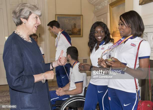 Britain's Prime Minister Theresa May speaks to 400m sprint and 400m hurdles athlete Perri ShakesDrayton and 4x100m athlete Asha Philip during a...