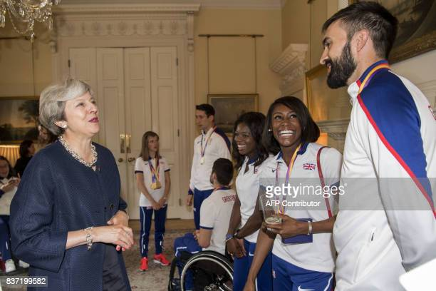 Britain's Prime Minister Theresa May speaks to 4x400 relay athlete Martyn Rooney as 400m sprint and 400m hurdles athlete Perri ShakesDrayton and...